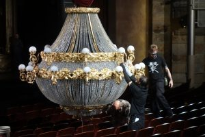 """""""Staff adjusts the chandelier prior to showtime.""""  Photo by Tom Jones."""
